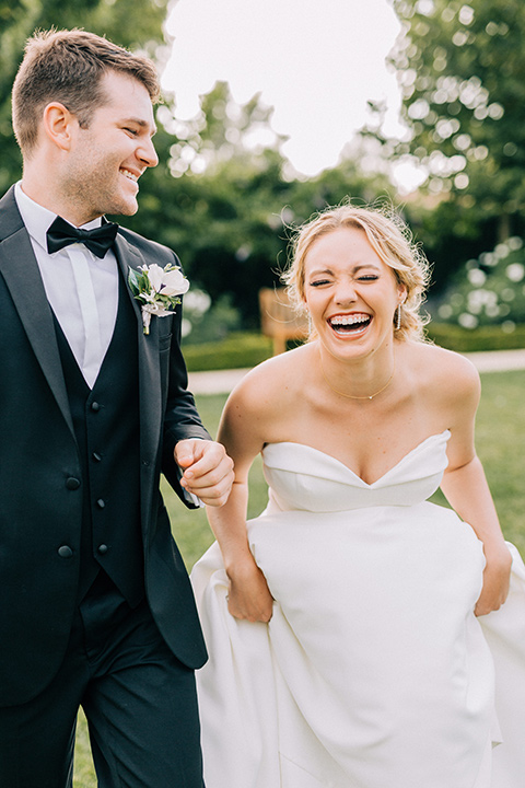 bride in a white strapless ballgown with her hair in a bun, groom in a black tuxedo with a black bow tie