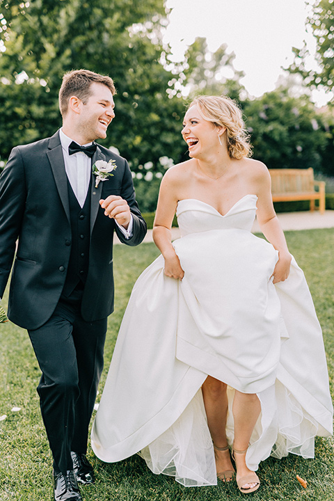 bride and groom running, bride in a white strapless ballgown with a bow detail and hair in a bun, groom in a black tuxedo with a black bow tie