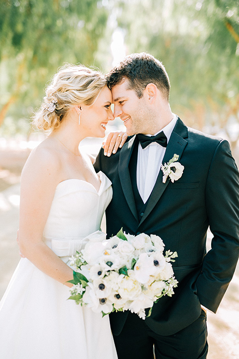 bride and groom touching heads, bride in a white strapless ballgown with a bow detail and hair in a bun, groom in a black tuxedo with a black bow tie