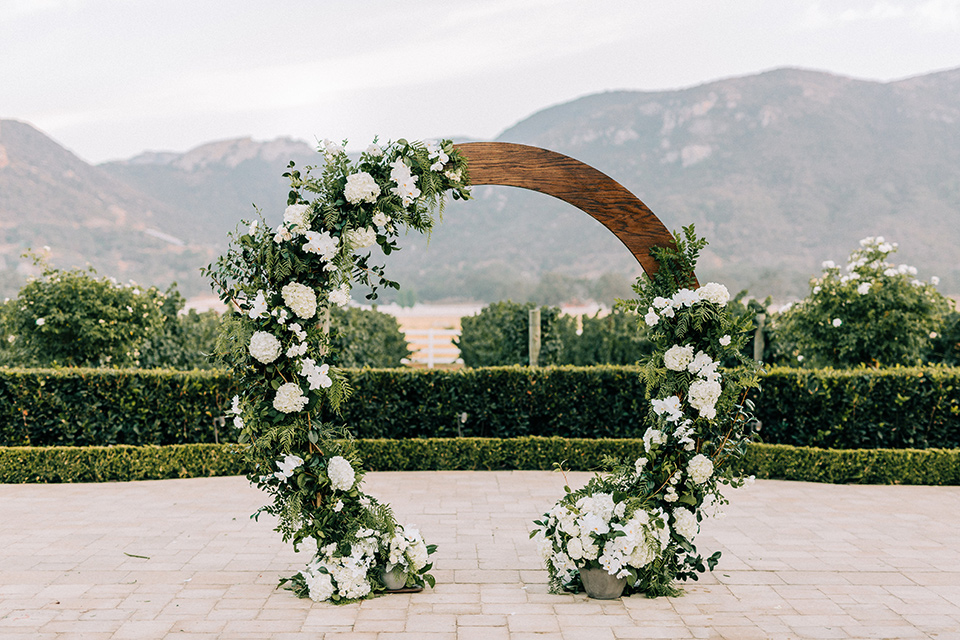 rounded ceremony arch with flowers on it