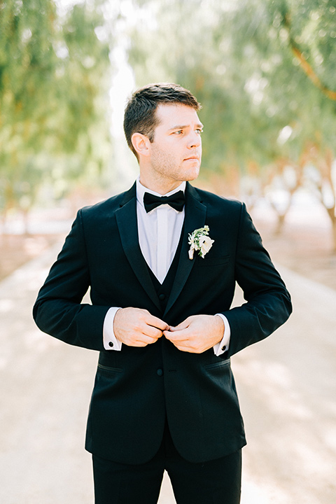 groom in a black tuxedo with a black bow tie