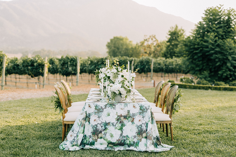 table set up with a floral table linen and wooden chairs with white candles and florals
