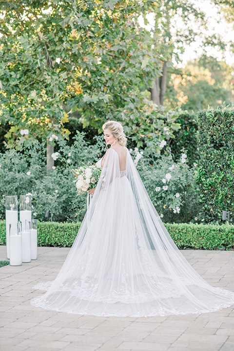 bride in a white gown with a plunging neckline and a sheer cape and train