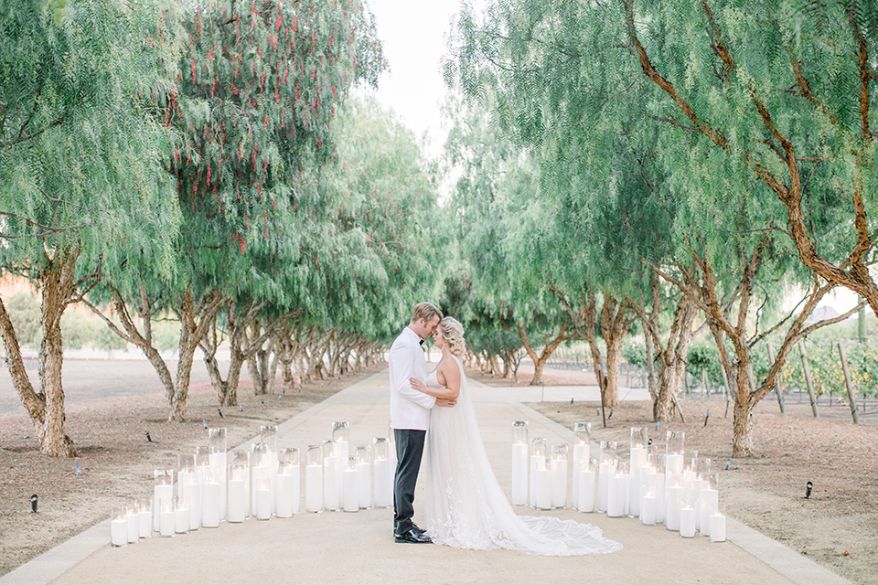 bride and groom by tall candles, bride in a white gown with a plunging neckline and a sheer cape and train and the groom in a white jacket and black pants