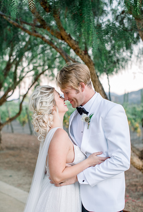 bride and groom close up, bride in a white gown with a plunging neckline and a sheer cape and train and the groom in a white jacket and black pants