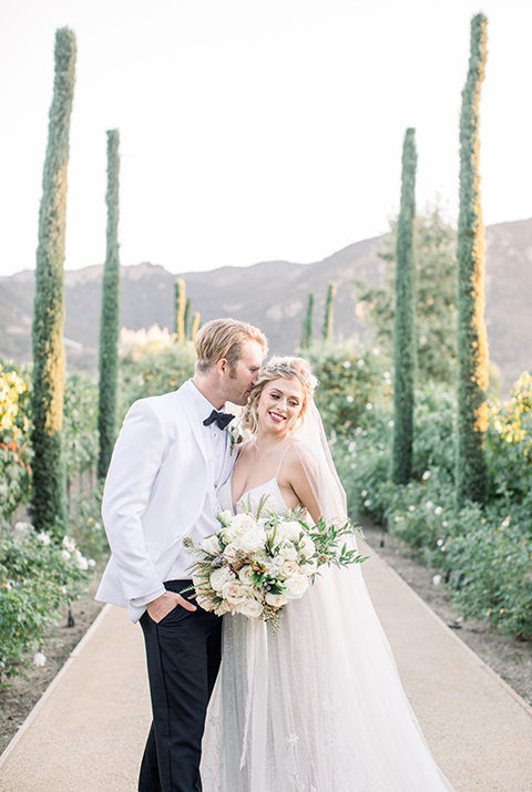 bride and groom by cypress trees, bride in a white gown with a plunging neckline and a sheer cape and train and the groom in a white jacket and black pants