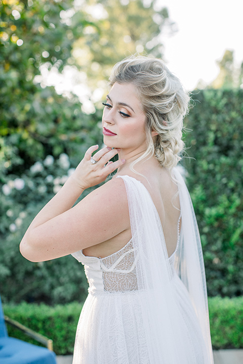 bride in a white gown with a plunging neckline and a sheer cape and train with her hair in a bun