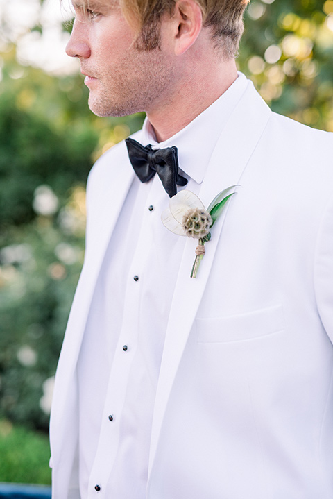 groom in a white jacket and black pants