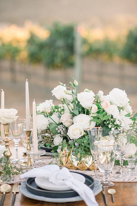wooden table with white florals and flatware