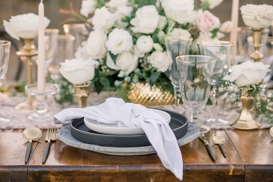 wooden table with white flatware and white florals