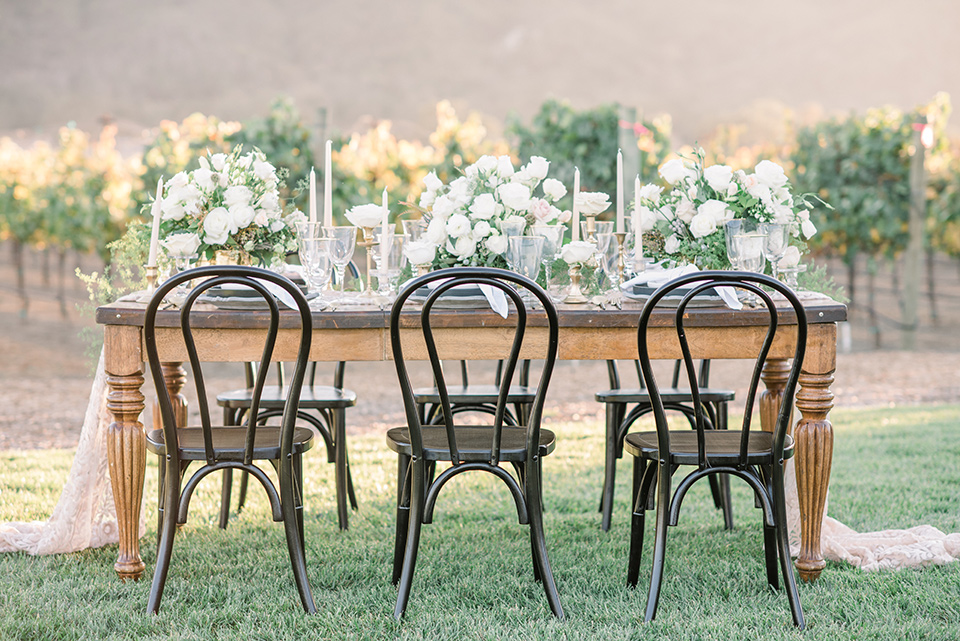 wooden table with white flatware and white florals and black chairs
