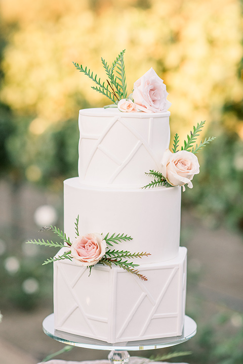 white three-tiered cake with pink floral designs