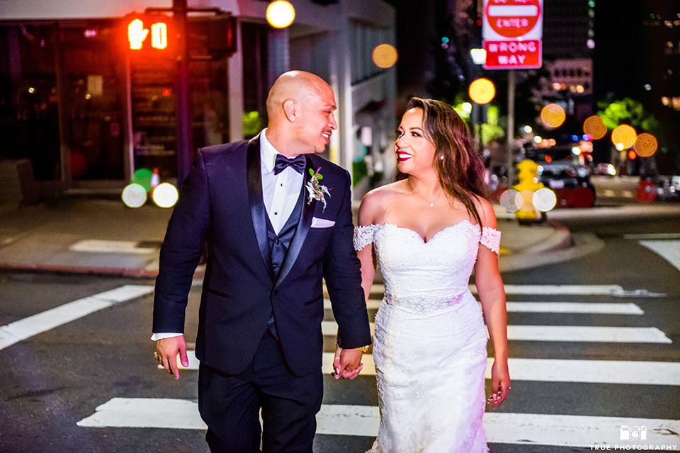San-Diego-Wedding-bride-and-groom-crossing-street-the-bride-is-in-a-lace-form-fitting-gown-with-an-off-the-shoulder-neckline-groom-is-in-a-black-tuxedo-with-a-black-bow-tie