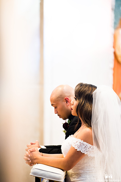 San-Diego-Wedding-bride-and-groom-kneeling-at-ceremony-the-bride-is-in-a-white-lace-gown-with-an-off-the-shoulder-neckline-groom-in-a-black-tuxedo-with-a-black-bow-tie