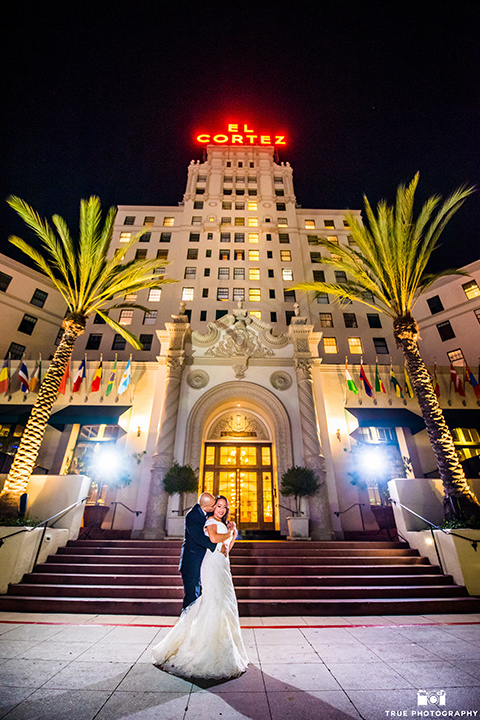 San-Diego-Wedding-bride-and-groom-outside-buiding-at-night-the-bride-is-in-a-white-lace-gown-with-an-off-the-shoulder-neckline-groom-in-a-black-tuxedo-with-a-black-bow-tie