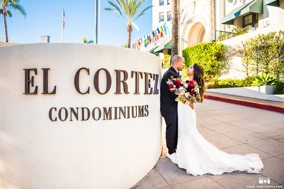 San-Diego-Wedding-bride-and-groom-outside-venue-the-bride-is-in-a-lace-form-fitting-gown-with-an-off-the-shoulder-neckline-groom-is-in-a-black-tuxedo-with-a-black-bow-tie
