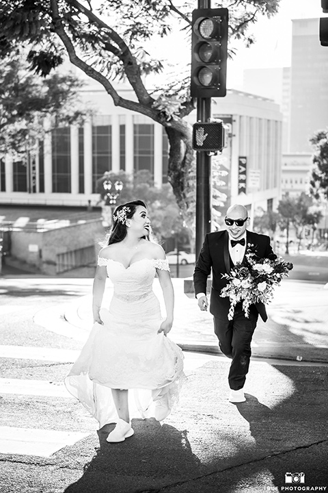 San-Diego-Wedding-bride-and-groom-running-bride-in-a-white-lace-gown-with-an-off-the-shoulder-neckline-groom-is-in-a-black-tuxedo-with-a-black-bow-tie