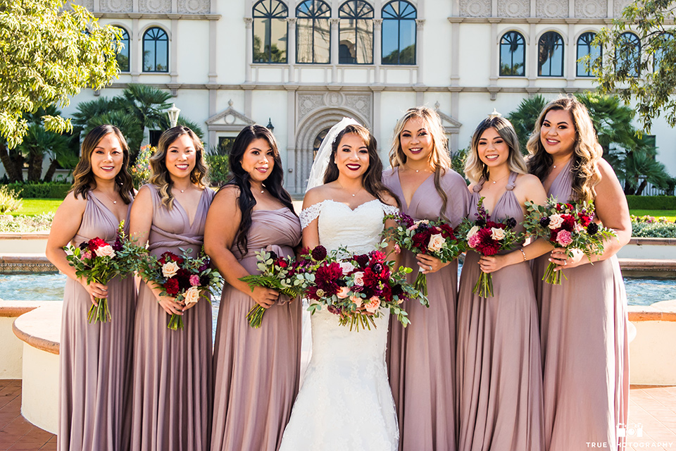 San-Diego-Wedding-bridesmaids-the-bride-is-in-a-lace-form-fitting-gown-with-an-off-the-shoulder-neckline-the-bridesmaids-in-mauve-pink-gowns