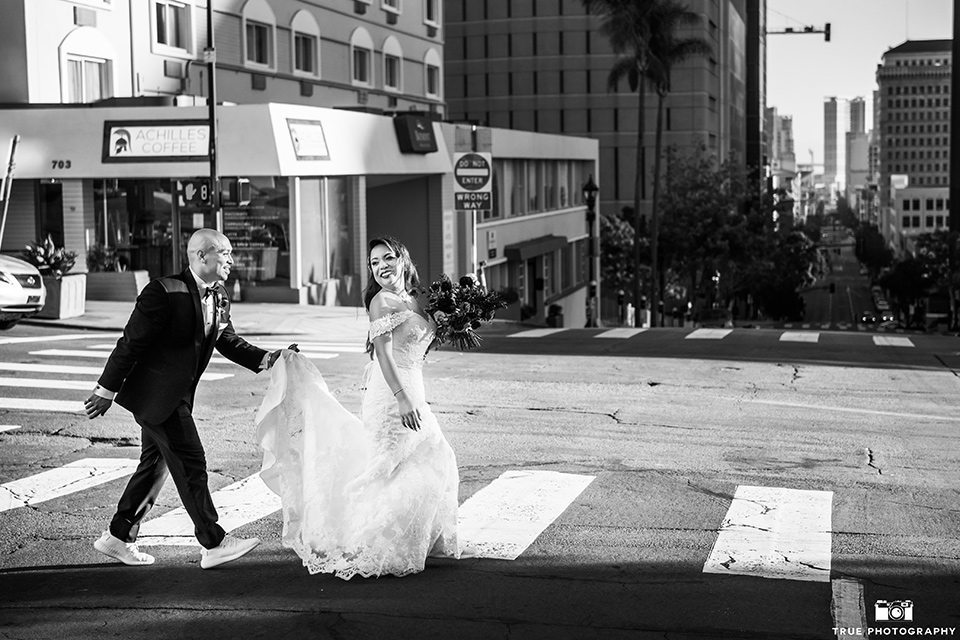 San-Diego-Wedding-groom-holding-brides-gown-crossing-the-street-bride-is-in-a-lace-form-fitting-gown-with-an-off-the-shoulder-neckline-groom-is-in-a-black-tuxedo-with-a-black-bow-tie