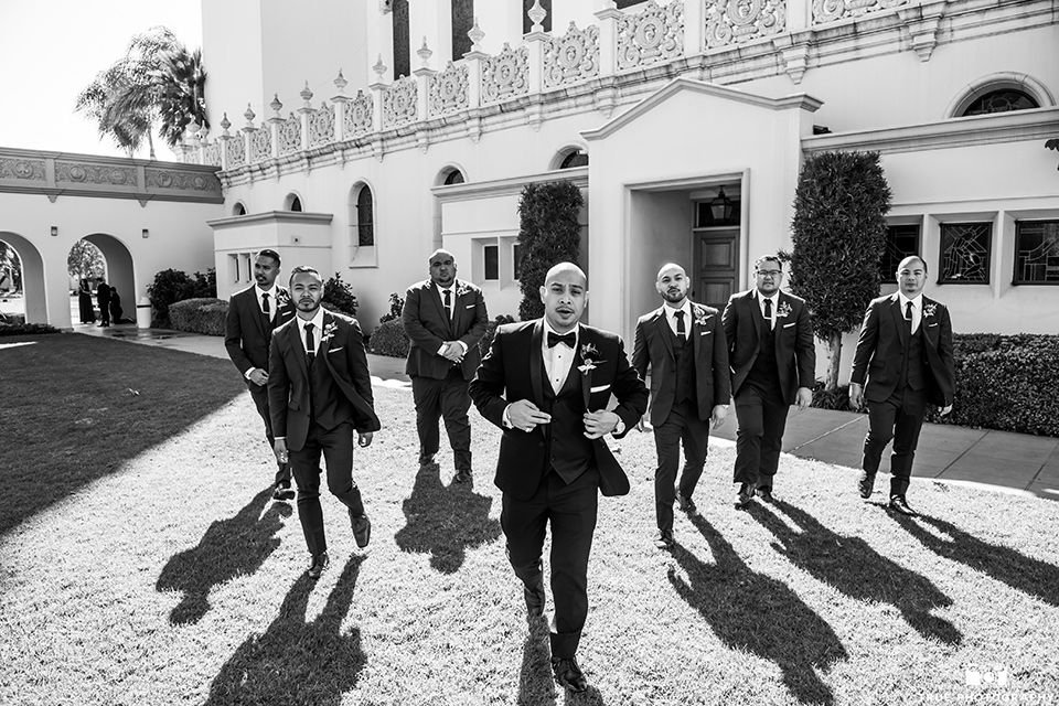 San-Diego-Wedding-groomsmen-standing-in-a-triangle-in-cobalt-suits-and-the-groom-is-in-a-black-tuxedo-with-a-black-bow-tie