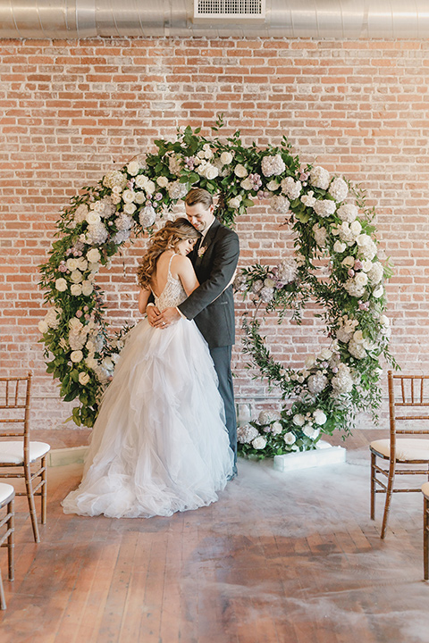 bride in a tulle white gown with a low back detail and a sweetheart neckline and the groom in a black notch lapel tuxedo with a black long tie and a floral circular arch