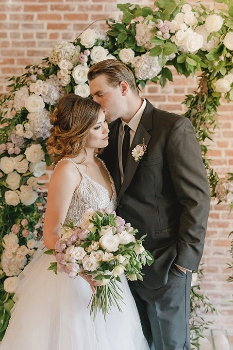 bride in a white tulle ballgown with a low back and a sweetheart neckline and the groom in a black tuxedo with a long black tie