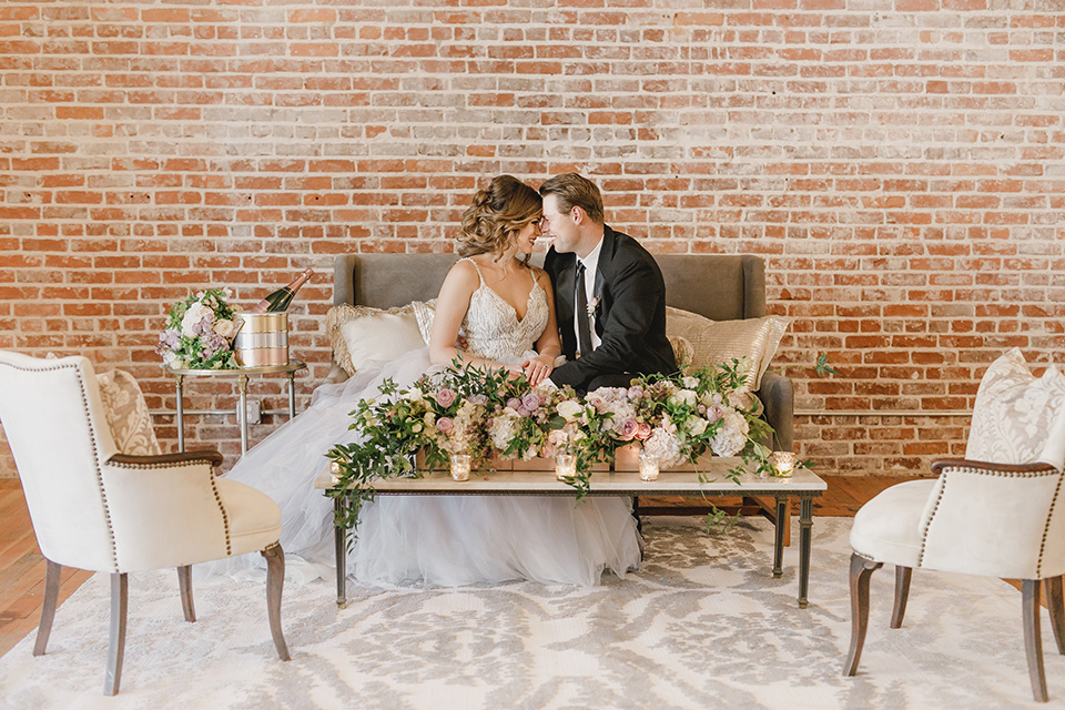 bride in a white tulle ballgown with a low back and a sweetheart neckline and the groom in a black tuxedo with a long black tie sitting on a couch