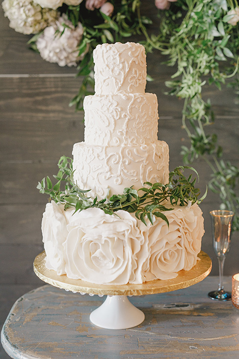 white three tiered cake with green leaf detailing