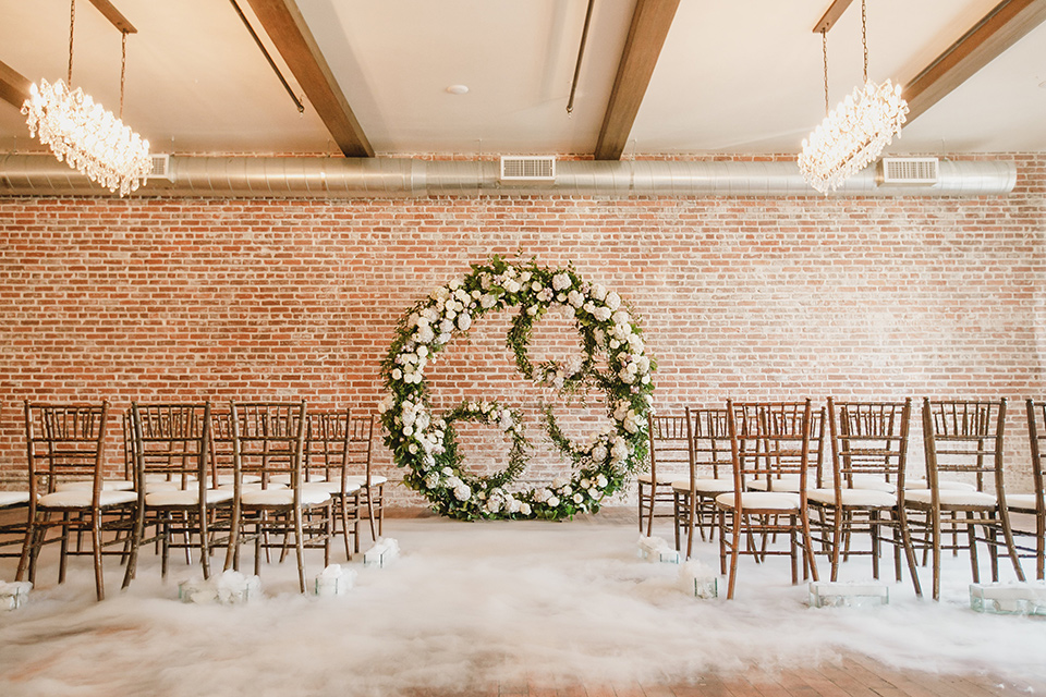 circular floral arch and wooden chairs, with a white faux fur carpet on the ground