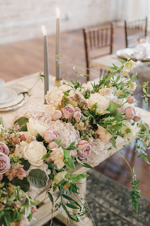 white pink and green florals with tall candles and white chairs