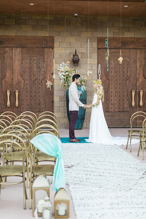 fazeli-winery-wedding-bride-and-groom-at-ceremony-bride-in-a-flowing-boho-strapless-gown-groom-in-a-tan-jacket-and-burgundy-pants