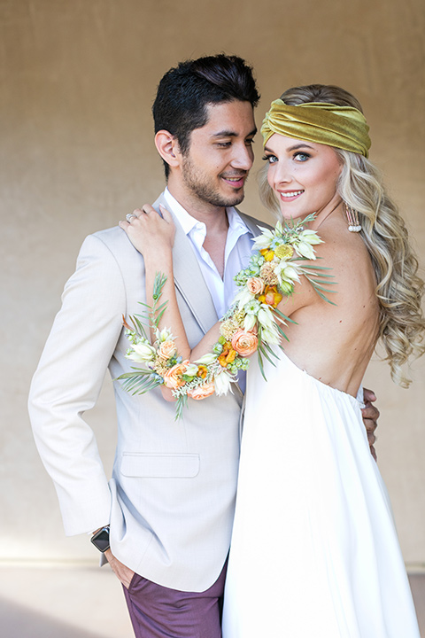 fazeli-winery-wedding-bride-and-groom-bride-looking-at-camera-and-groom-looking-at-her-bride-in-a-flowing-boho-strapless-gown-groom-in-a-tan-jacket-and-burgundy-pants