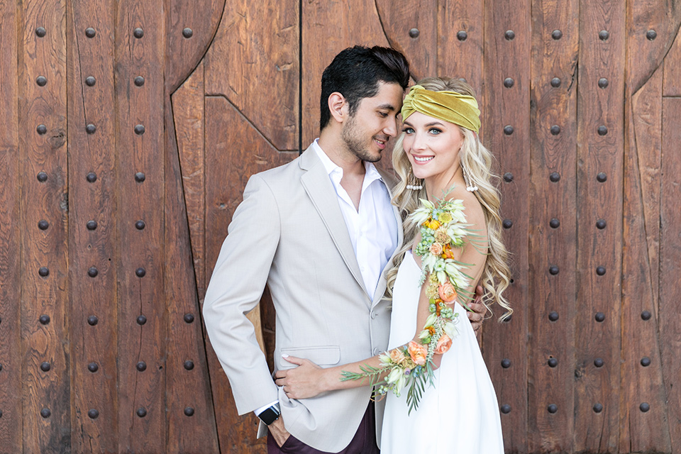 fazeli-winery-wedding-bride-and-groom-by-wooden-door-bride-looking-at-camera-bride-in-a-sheath-strapless-dress-and-a-floral-headpiece-groom-in-a-tan-coat-and-burgundy-pants