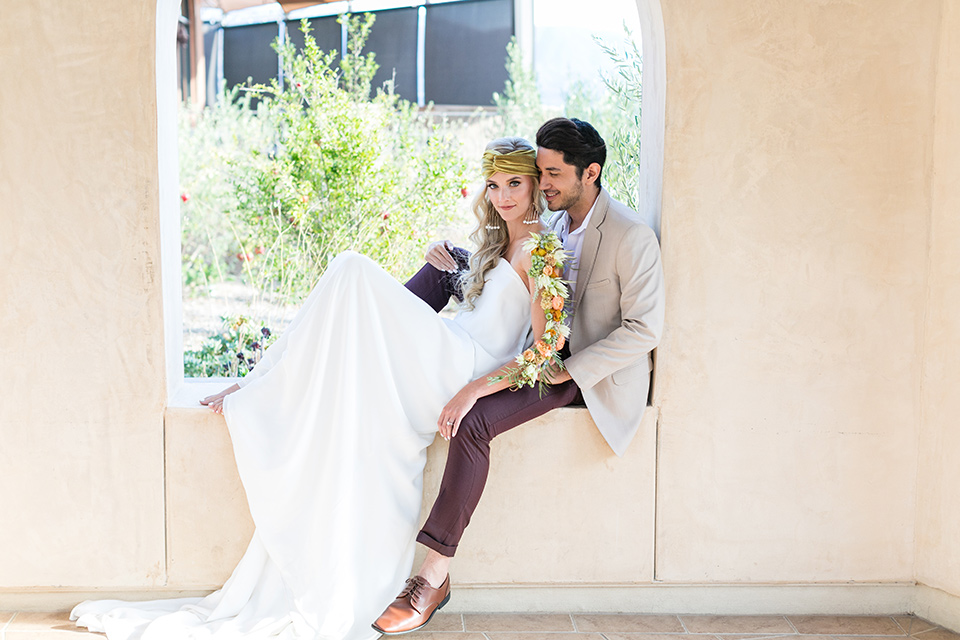 fazeli-winery-wedding-bride-and-groom-in-windowpayne-bride-in-a-sheath-strapless-dress-and-a-floral-headpiece-groom-in-a-tan-coat-and-burgundy-pants