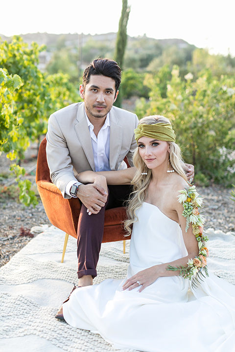 fazeli-winery-wedding-bride-and-groom-sitting-in-vineyard-bride-in-a-long-sheath-white-gown-with-a-floral-headpiece-and-flowers-on-her-arm-groom-in-a-tan-suit-coat-and-burgundy-pants