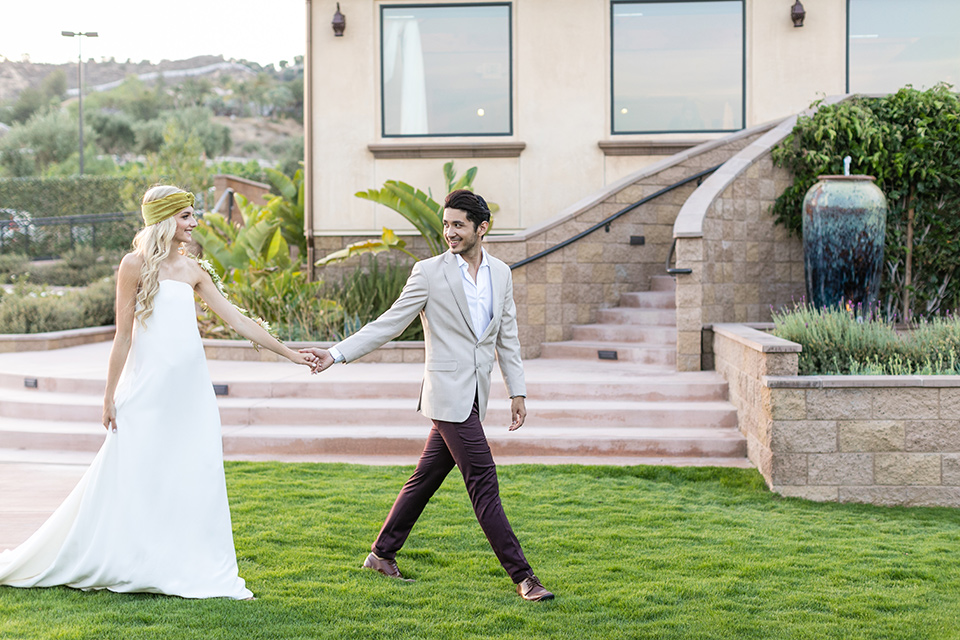 fazeli-winery-wedding-bride-and-groom-walking-bride-in-a-sheath-strapless-dress-and-a-floral-headpiece-groom-in-a-tan-coat-and-burgundy-pants