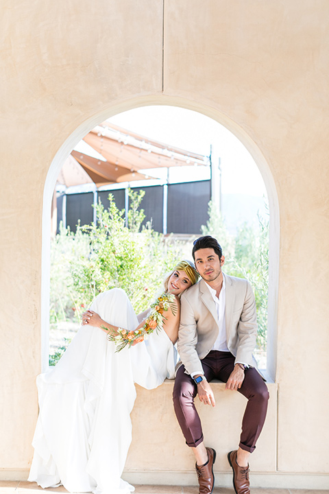 fazeli-winery-wedding-bride-with-her-feet-up-and-groom-with-feet-on-the-ground-facing-camera-bride-in-a-long-sheath-white-gown-with-a-floral-headpiece-and-flowers-on-her-arm-groom-in-a-tan-suit-coat-and-burgundy-pants