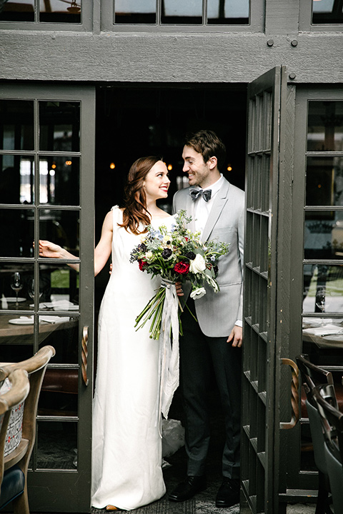 bride in a white lace gown with cap sleeves and a light grey suit coat and black pants with a grey velvet bow tie
