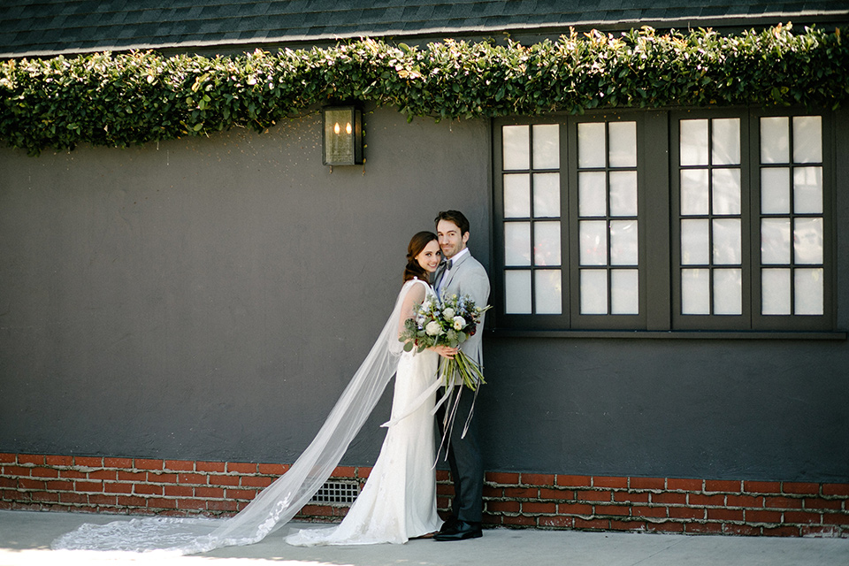 The bride in a white gown with lace long sleeves and a high neckline the groom in a light grey suit with black pants and a grey velvet bow tie