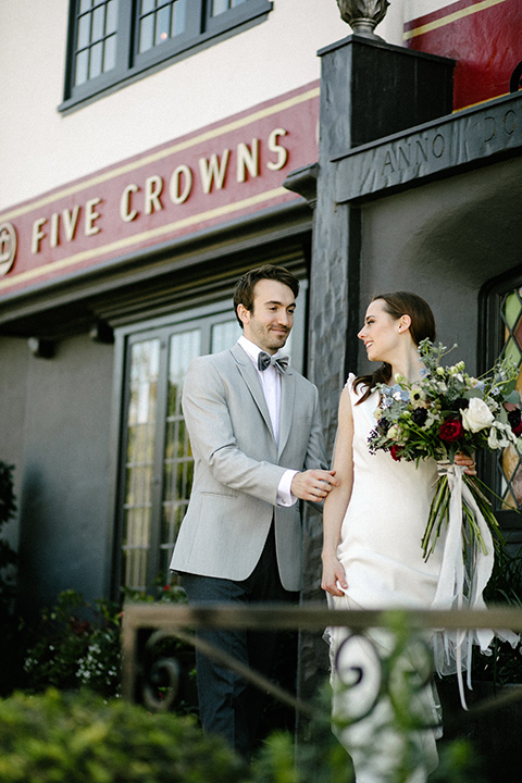 bride in a white flowing gown with long and high neckline sleeves and the groom in a grey suit coat with a pair of black pants and a velvet grey bow tie