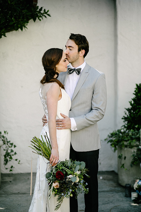 bride in a white flowing gown with cap sleeves and the groom in a grey suit coat with a pair of black pants and a velvet grey bow tie