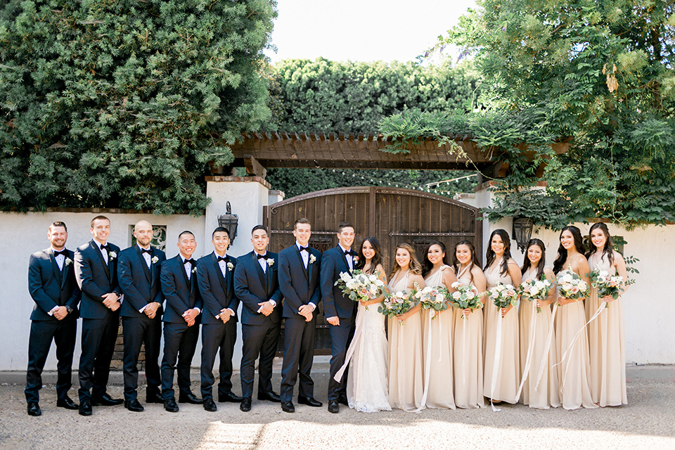 franciscan-gardens-wedding-bridal-party-lined-up-bridesmaids-in-a-light-chamagne-color-groomsmen-in-navy-suits-bride-in-a-white-mermaid-strapless-gown-with-hair-down-and-simple-groom-in-a-navy-shawl-lapel-tuxedo-with-a-black-bow-tie