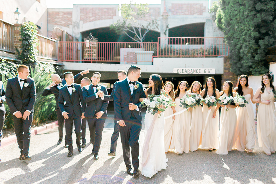 franciscan-gardens-wedding-bridal-party-walking-bridesmaids-in-a-light-chamagne-color-groomsmen-in-navy-suits-bride-in-a-white-mermaid-strapless-gown-with-hair-down-and-simple-groom-in-a-navy-shawl-lapel-tuxedo-with-a-black-bow-tie