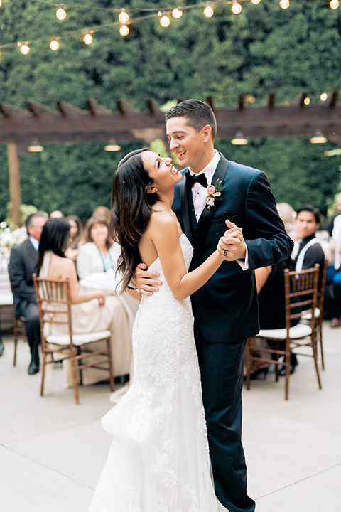 franciscan-gardens-wedding-bride-and-groom-dancing-bride-in-a-mermaid-white-strapless-gown-with-hair-down-in-a-simple-wave-and-groom-in-a-dark-blue-tuxedo-with-a-black-shawl-lapel-and-black-bow-tie