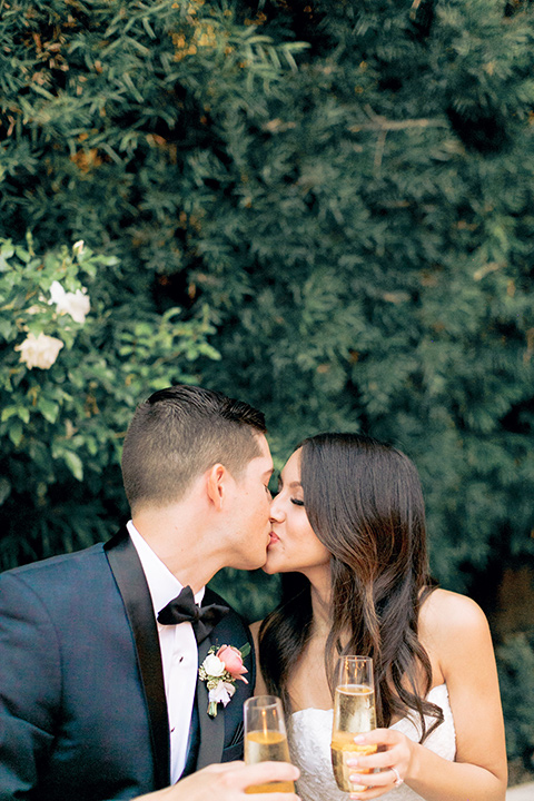 franciscan-gardens-wedding-bride-and-groom-kissing-bride-in-a-strapless-form-fitting-white-gown-groom-in-a-navy-shawl-lapel-tuxedo-with-black-accessories