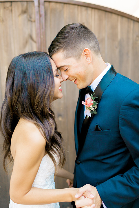 franciscan-gardens-wedding-bride-and-groom-touching-heads-bride-in-a-mermaid-white-strapless-gown-with-hair-down-in-a-simple-wave-and-groom-in-a-dark-blue-tuxedo-with-a-black-shawl-lapel-and-black-bow-tie