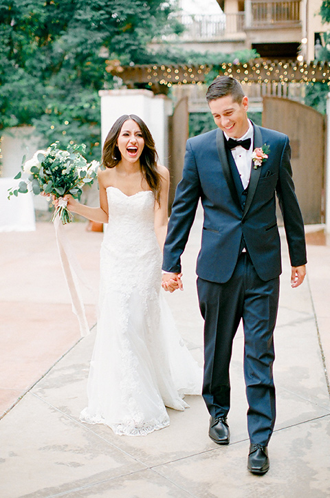 franciscan-gardens-wedding-bride-and-groom-walking-and-smiling-bride-in-a-strapless-form-fitting-white-gown-groom-in-a-navy-shawl-lapel-tuxedo-with-black-accessories