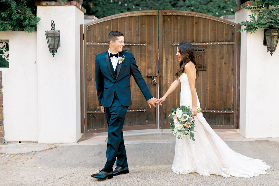 franciscan-gardens-wedding-bride-and-groom-walking-groom-looking-back-at-her-bride-in-a-white-mermaid-strapless-gown-with-hair-down-and-simple-groom-in-a-navy-shawl-lapel-tuxedo-with-a-black-bow-tie