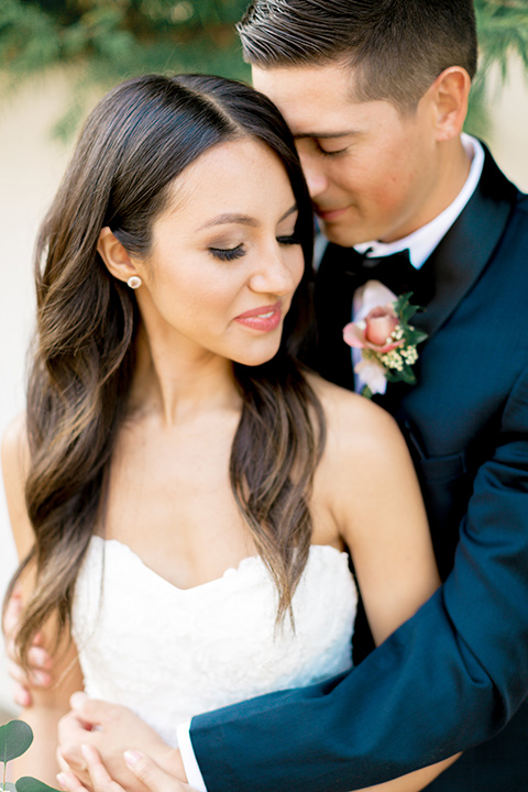 franciscan-gardens-wedding-close-up-of-bride-and-groom-bride-in-a-mermaid-white-strapless-gown-with-hair-down-in-a-simple-wave-and-groom-in-a-dark-blue-tuxedo-with-a-black-shawl-lapel-and-black-bow-tie