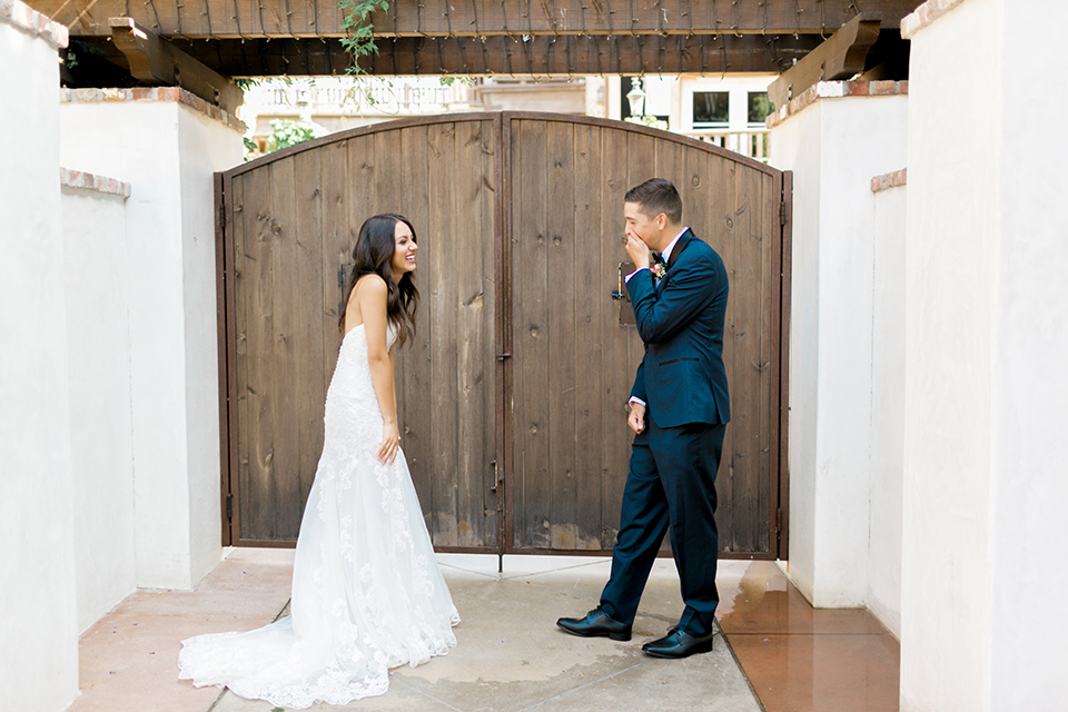 franciscan-gardens-wedding-first-look-bride-in-a-white-mermaid-strapless-gown-with-hair-down-and-simple-groom-in-a-navy-shawl-lapel-tuxedo-with-a-black-bow-tie
